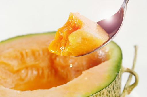 用勺子將半切瓜果肉撈出時滴上一滴果汁