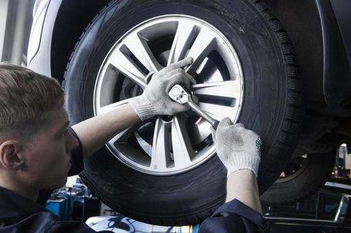 Automobile mechanic servicing tires 11