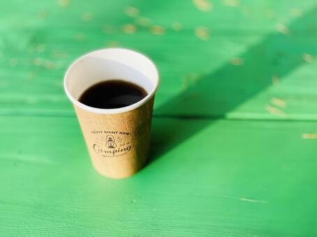 1 paper cup coffee on a green table