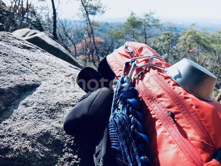 岩場に置かれた登山用リュックの写真