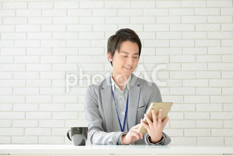 タブレットを操作している男性の写真