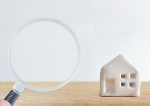 House model and magnifying glass