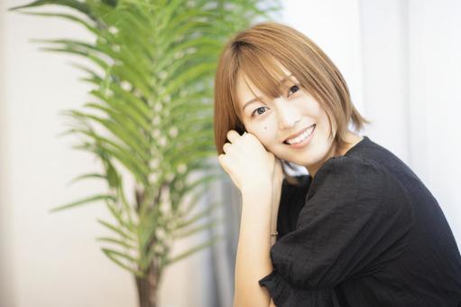 A smiling woman beside a houseplant