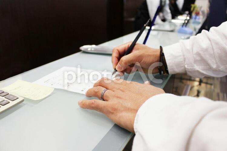 カウンターで手続きをする人の写真