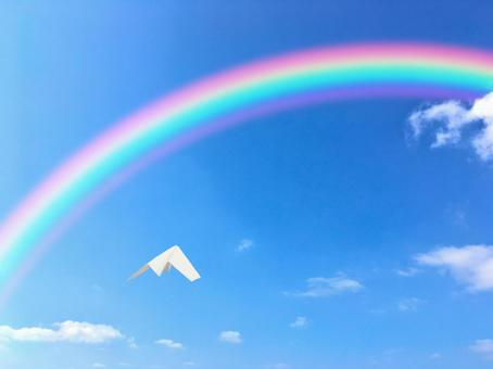 Paper plane flying towards the blue sky and the rainbow 1