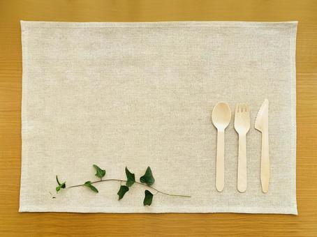 Wooden cutlery, ivy leaves and a natural placemat