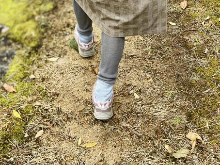 The feet of a woman walking on a country road