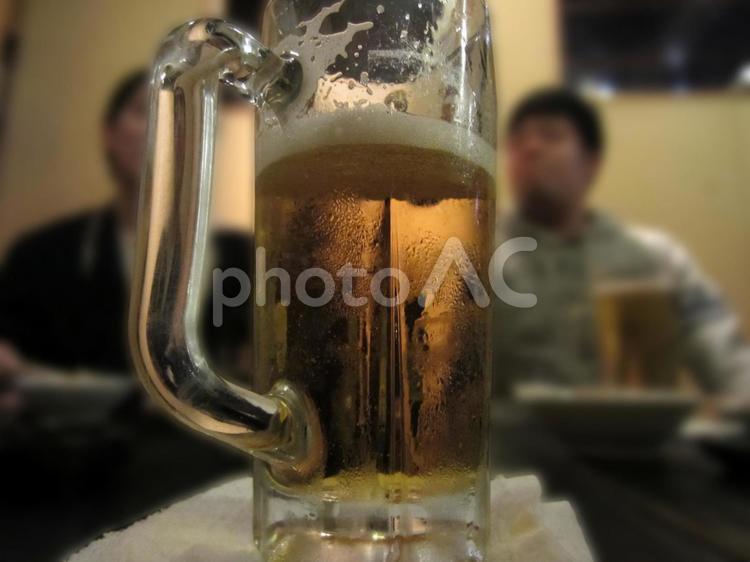 おしぼりをコースターにしてビールジョッキを置くの写真