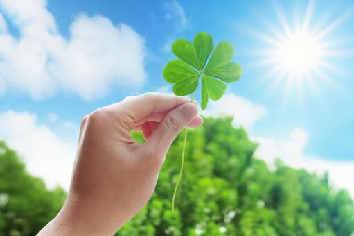 Hand with four-leaf clover, blue sky and sun