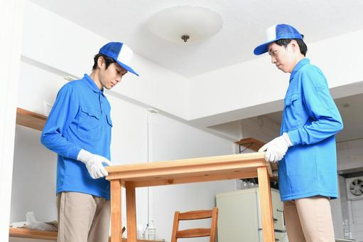 Image of multiple men wearing work clothes carrying a table during moving work