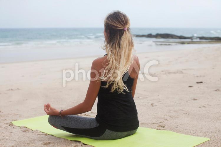 浜辺でヨガをする外国人の女性15の写真