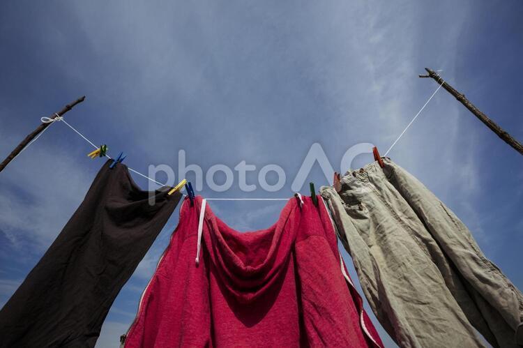 赤いパーカーとパンツの外干し1の写真