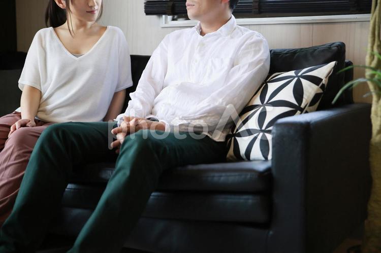ソファでくつろぐ男女の写真