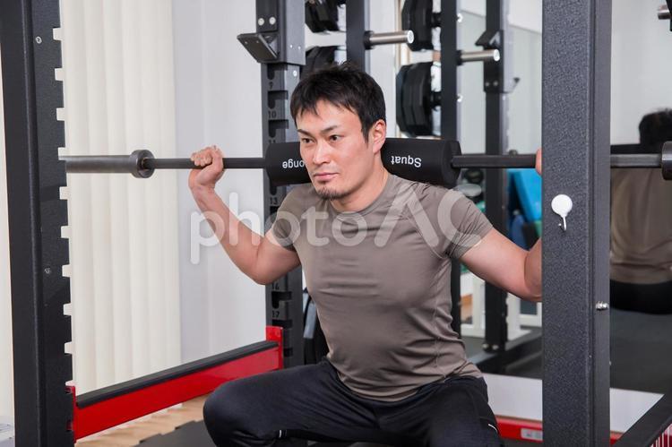 スポーツジムでスクワットする男性の写真