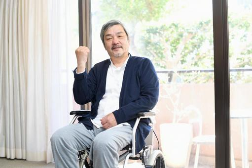 A smiling senior man in a wheelchair while taking a guts pose