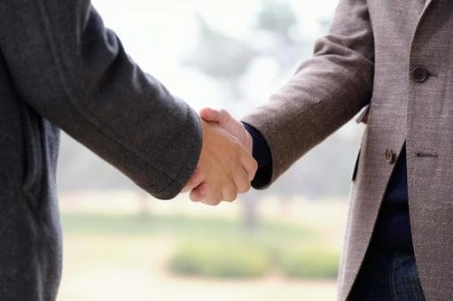 Image of shaking hands outdoors