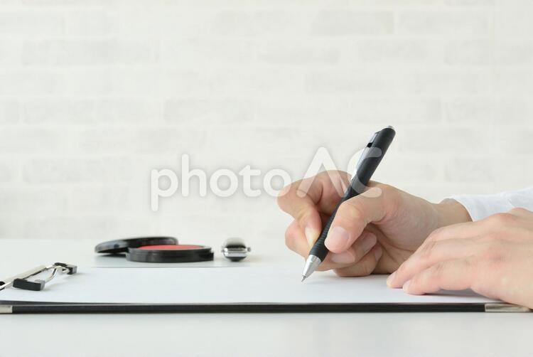契約書にサインする人物の手の写真