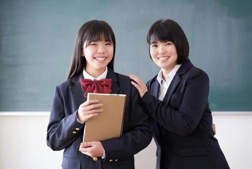 Japanese junior high school girls and teachers standing in the classroom with a smile