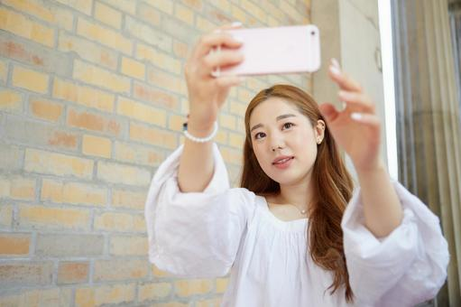 Asian women taking a selfie with a smartphone 8