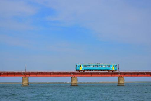 A blue vehicle running on a red iron bridge