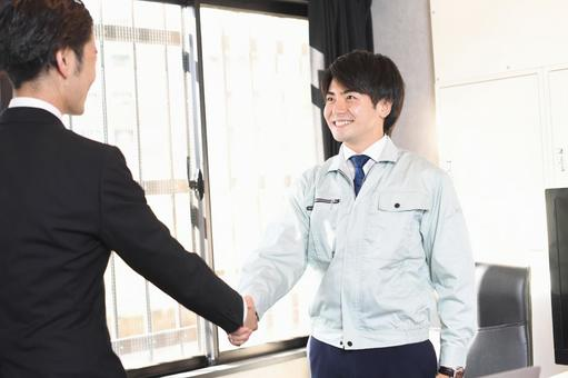 A businessman in work clothes shaking hands and a man in a suit