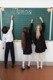 小学学生在黑板上写9