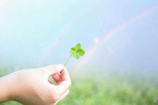 A hand with a clover and a rainbow of happiness