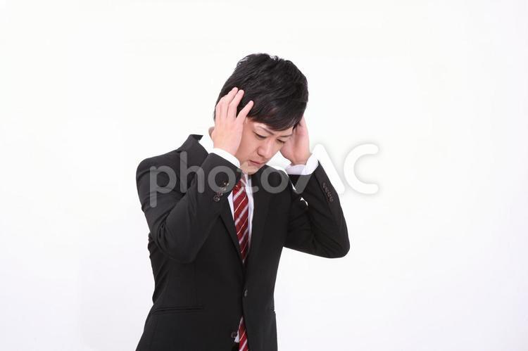 頭を抱えるサラリーマンの写真