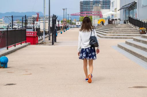 Back view of a woman walking along the beach