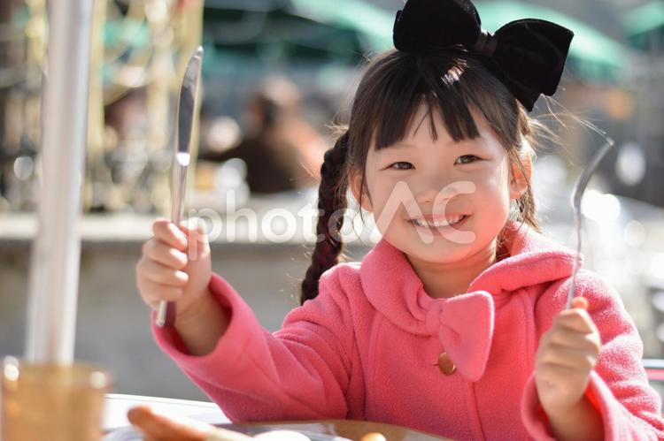 ナイフとフォークを持つ子供の写真