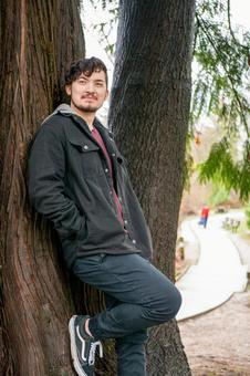 A smiling foreign man leaning under a tree Vertical photo