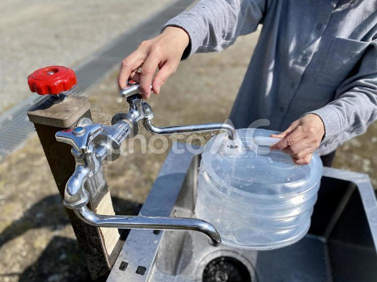キャンプ場でウォータージャグに水を入れる手の写真
