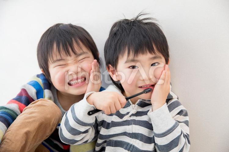 歯を抑える兄弟の写真