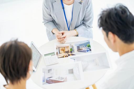 一個穿西裝的女人向男人和女人出售房地產