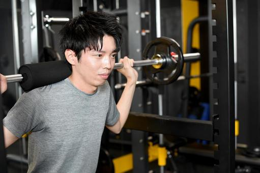 A young man doing muscle training (squats) in the gym