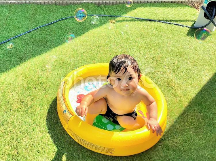 庭でプール遊びをする子供とシャボン玉の写真