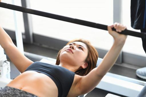 Young woman doing bench press at the gym