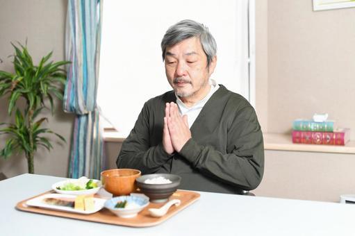 Elderly gray-haired man eating