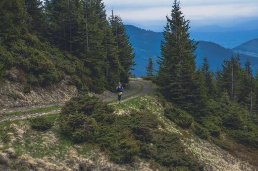 A woman running on a mountain path 1