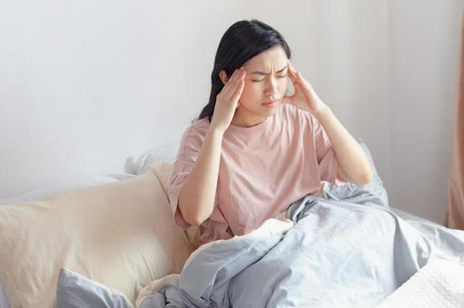 A woman holding her temples in bed