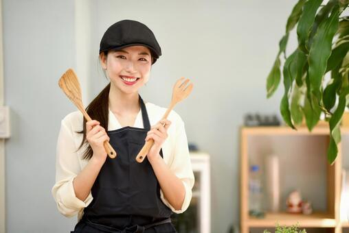 Woman with kitchen utensils