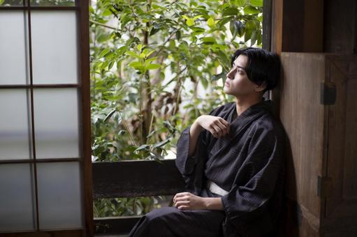 Yukata man sitting by the window and cooling down