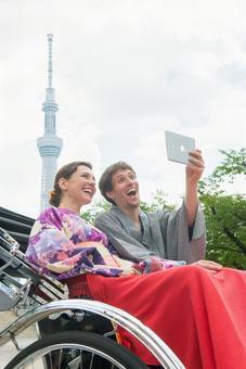 Foreign tourist couple 2 in a yukata taking a rickshaw