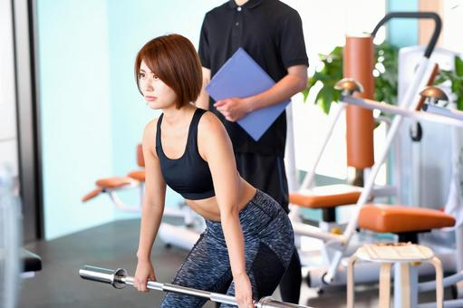 Trainer and young woman doing deadlift