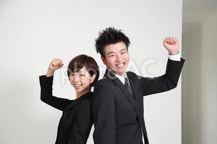 背中合わせでガッツポーズする会社員2の写真