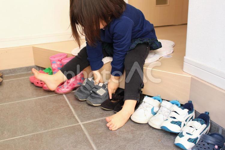 玄関で自分の靴を並べる子供の写真