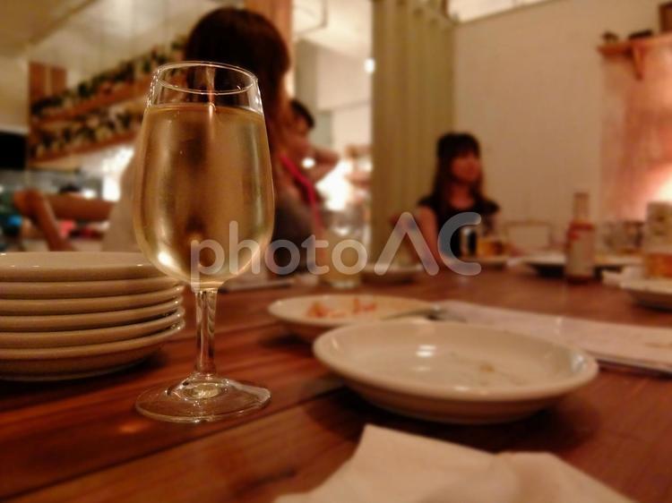 ワイングラス越しの女性が会話している飲み会の風景の写真