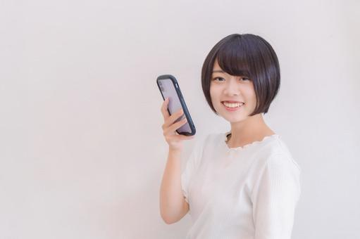 A woman who looks happily with her smartphone