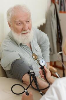 A foreign elderly man whose blood pressure is measured
