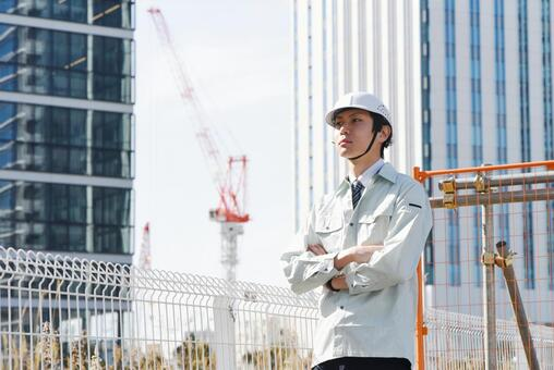 A man with a crane and arms folded